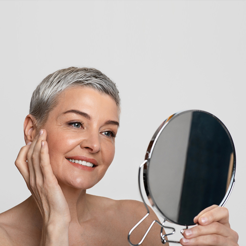 Photo of a middle aged woman with gray hear smiling at her image in the mirror since she's happily aging beautifully