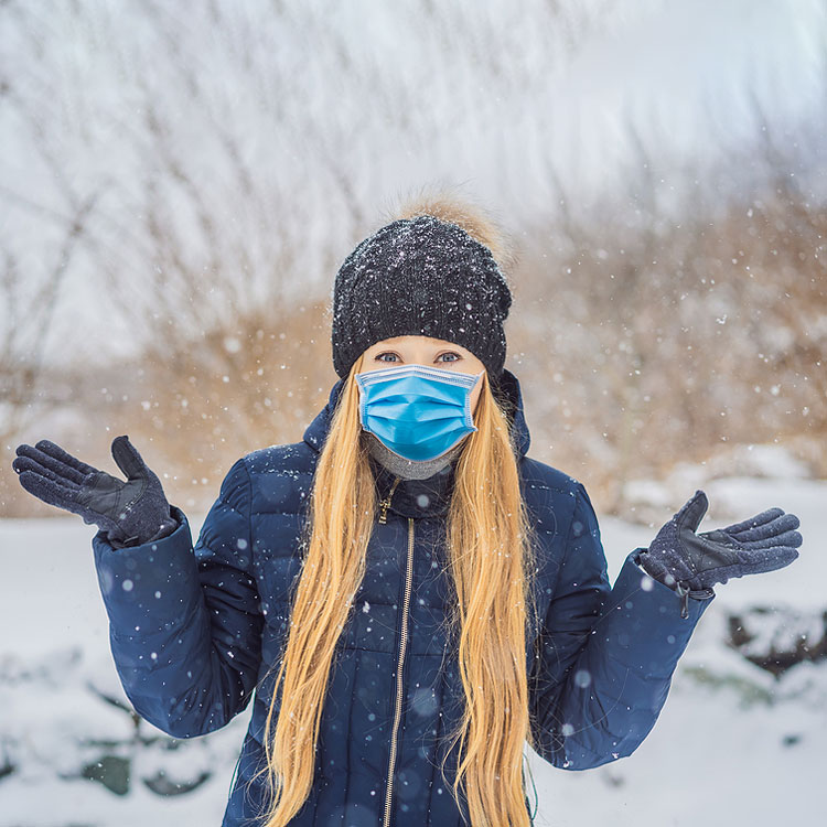 Woman standing in snow wearing puffy coat, with gloves, hat and medical mask