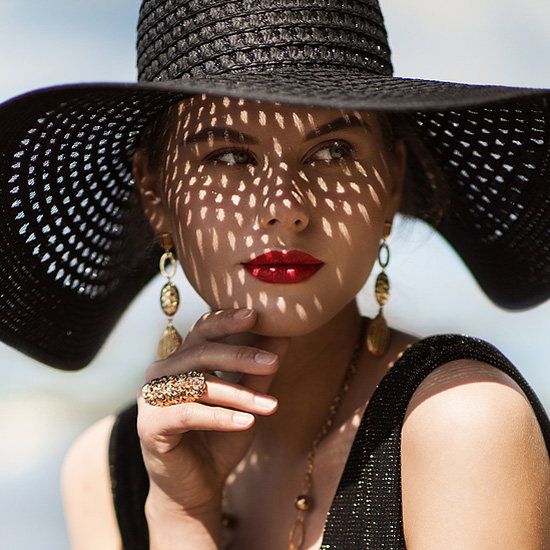 Beautiful woman wearing summer hat demonstrating how to care for your summer skin.